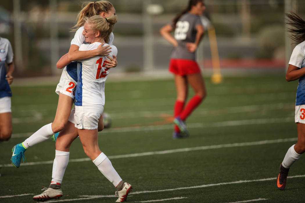Bishop Gorman's Jacqueline Hillegas, 23, is embraced by Kevyn Hillegas, 12, after scoring a goal against Arbor View High School during a game at Bishop Gorman High School in Las Vegas on Aug. 31,  ...