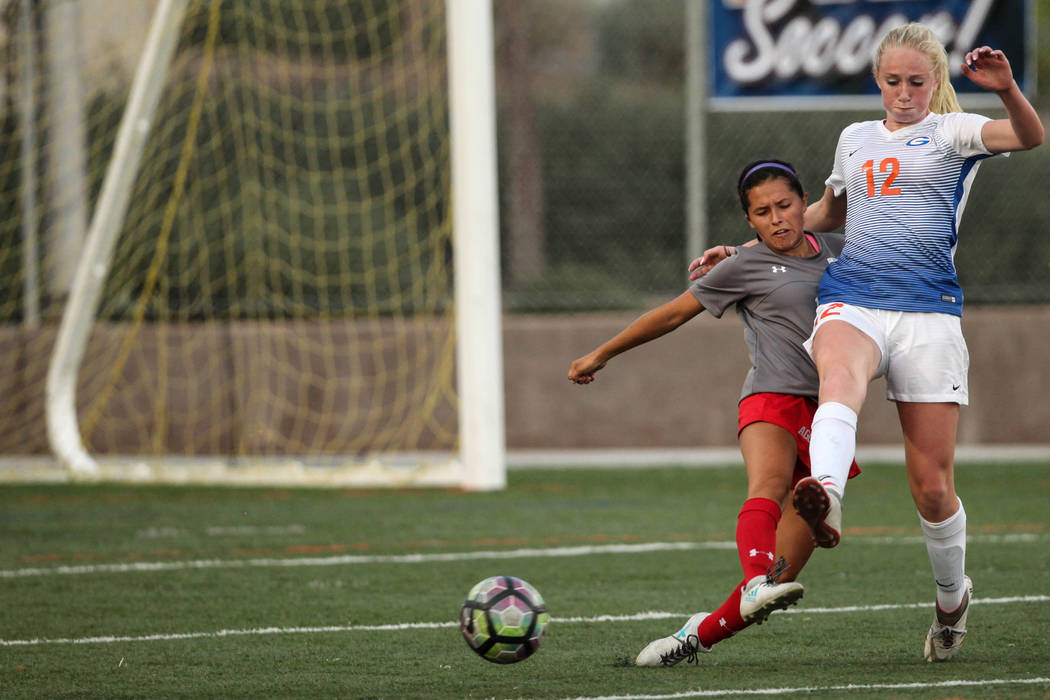 Arbor View High School's Sierra Vicente, 1, and Bishop Gorman's Kevyn Hillegas, 12, fight over the ball during a game at Bishop Gorman High School in Las Vegas on Aug. 31, 2017. Bishop Gorman won  ...