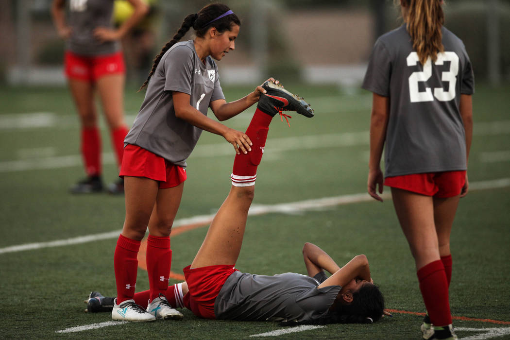 Arbor View High School's Sierra Vicente, 1, helps her teammate Karissa Martinez, 21, after cramping up during a game against Bishop Gorman at Bishop Gorman High School in Las Vegas on Aug. 31, 201 ...