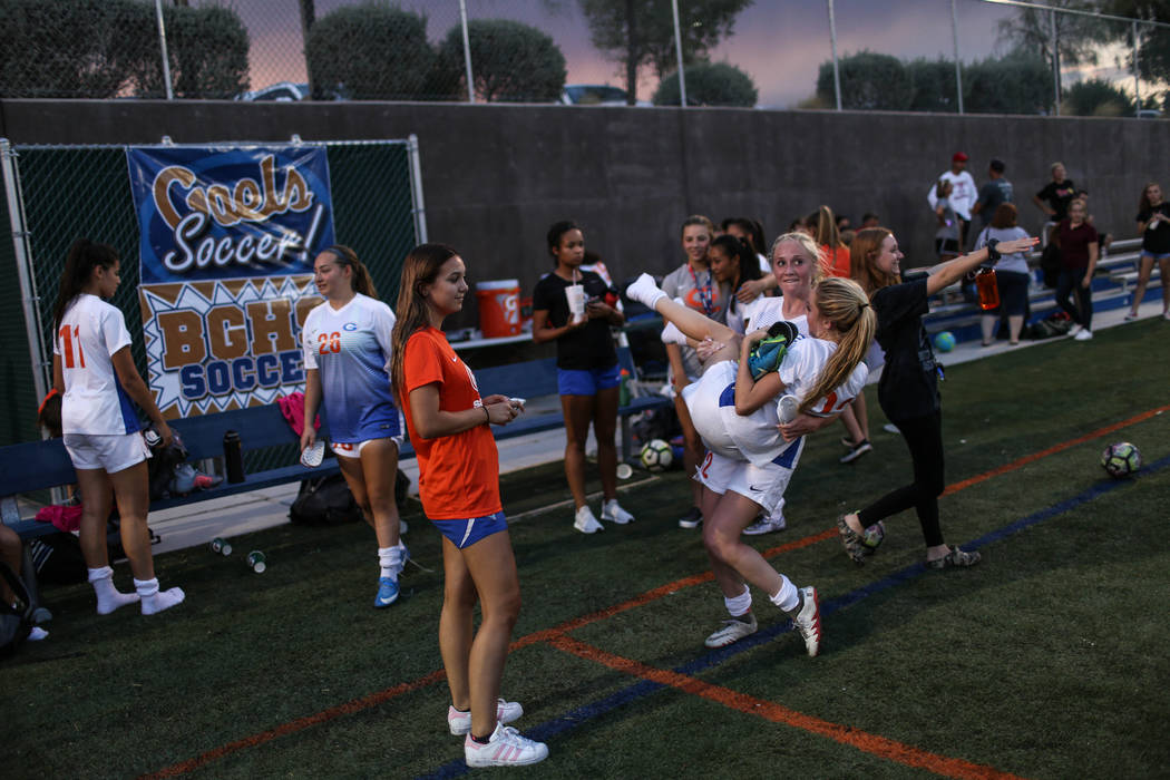 Bishop Gorman's Jacqueline Hillegas, 23, is carried by Kevyn Hillegas, 12, at the end of a game against Arbor View at Bishop Gorman High School in Las Vegas on Aug. 31, 2017. Bishop Gorman won 4-3 ...