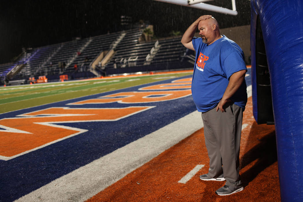 Bishop Gorman Assistant Coach Scott Cooley rubs his head during a delay at the Bishop Gorman versus Miami Central football game at Bishop Gorman High School in Las Vegas, Friday, Sept. 8, 2017. Jo ...