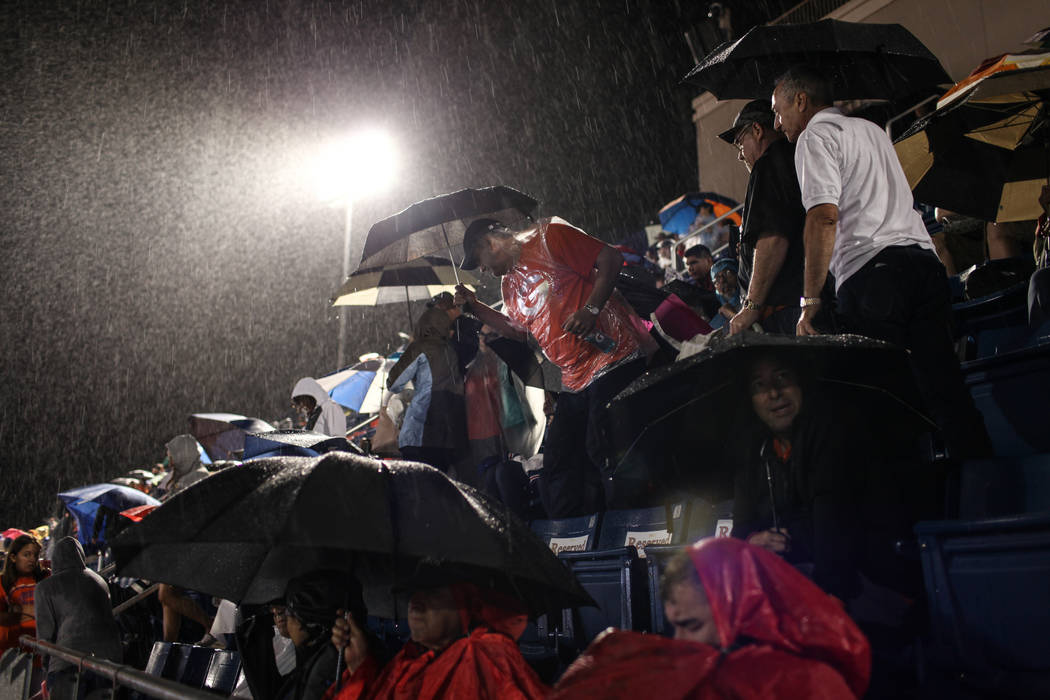 Fans sit in the rain during a delay at the Bishop Gorman versus Miami Central football game at Bishop Gorman High School in Las Vegas, Friday, Sept. 8, 2017. Joel Angel Juarez Las Vegas Review-Jou ...