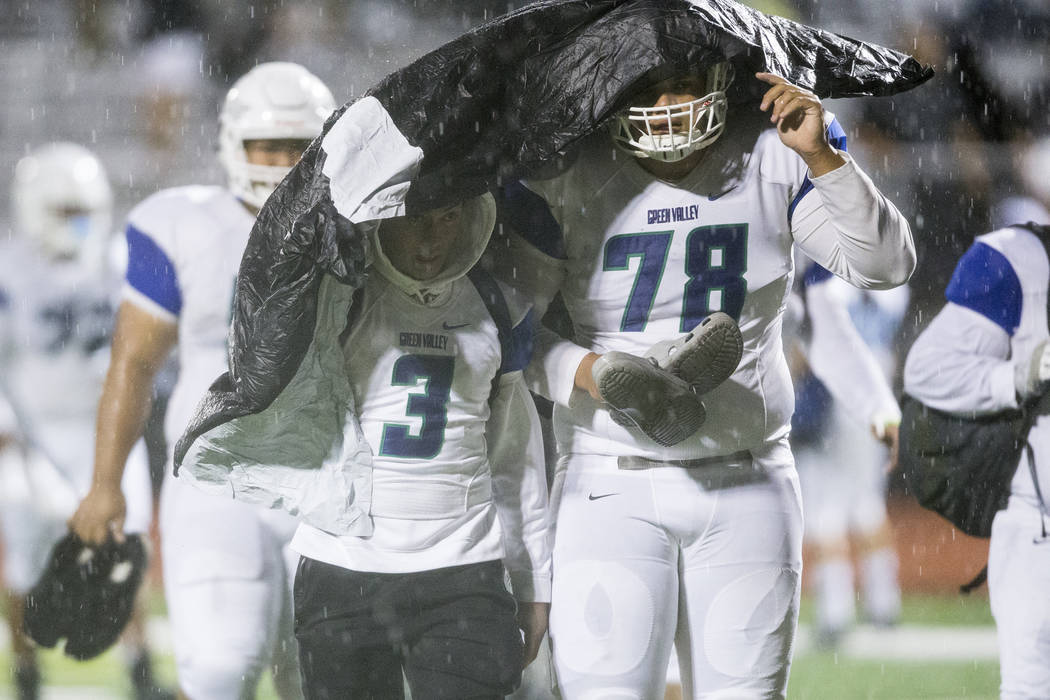 Green Valley's Christian Mayberry (3), and Eric Brown (78) leave the field due to a weather delay in their football game against Faith Lutheran at Faith Lutheran Middle School and High School in L ...
