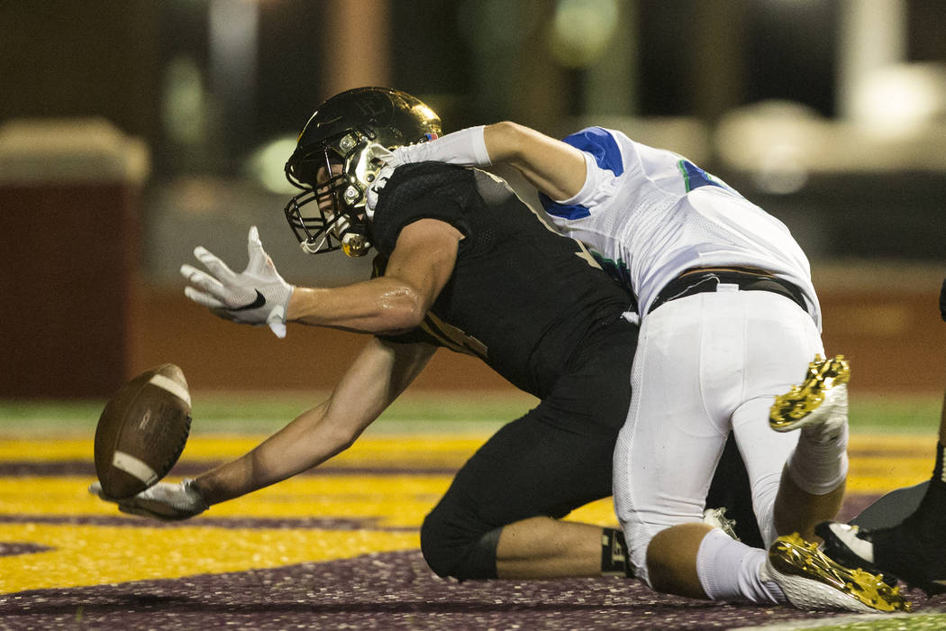Faith Lutheran's Peyton Thornton (14) drops the ball against Green Valley's Steeler Harms (23) in the football game at Faith Lutheran Middle School and High School in Las Vegas, on Monday, Aug. 21 ...