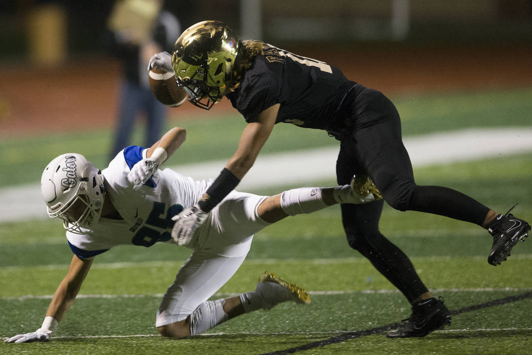 Faith Lutheran's Taimani McKenzie (10) deflects a pass to Green Valley's Adrian Gutierrez (85) in the football game at Faith Lutheran Middle School and High School in Las Vegas, on Monday, Aug. 21 ...