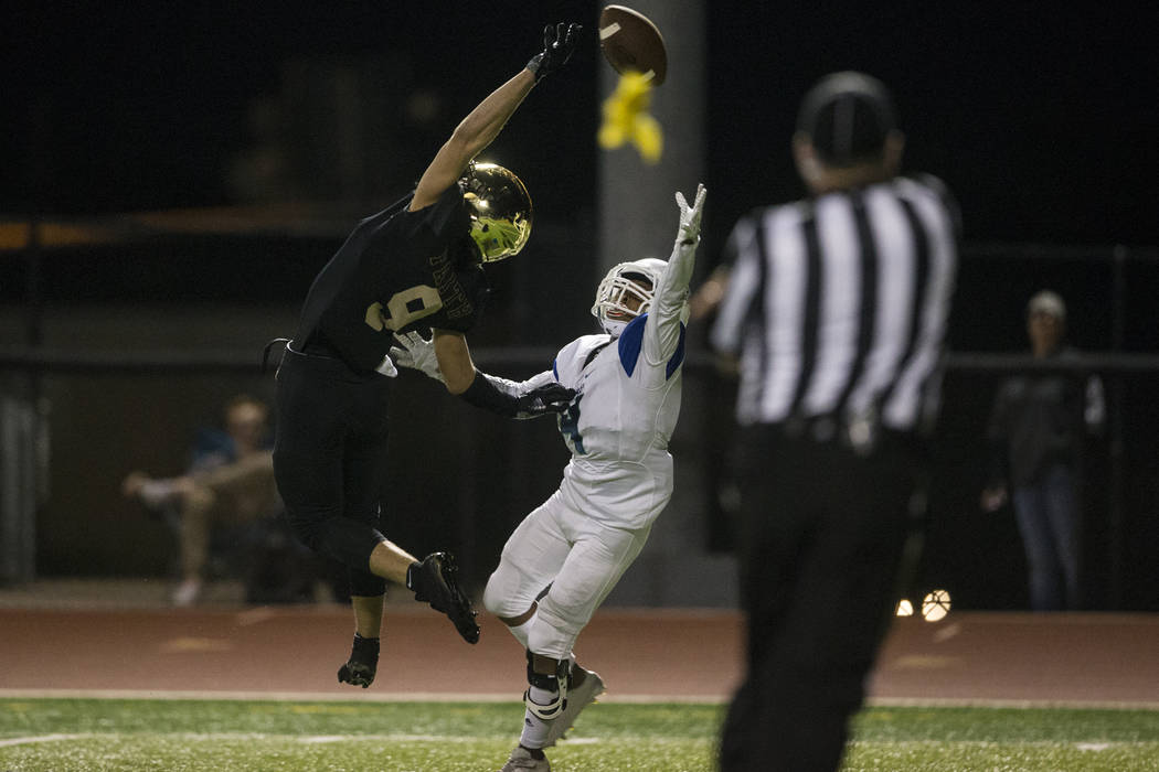 Faith Lutheran's Keagan Touchstone (9) leaps for the ball against Green Valley's TJ Saxon (4) in the football game at Faith Lutheran Middle School and High School in Las Vegas, on Monday, Aug. 21, ...
