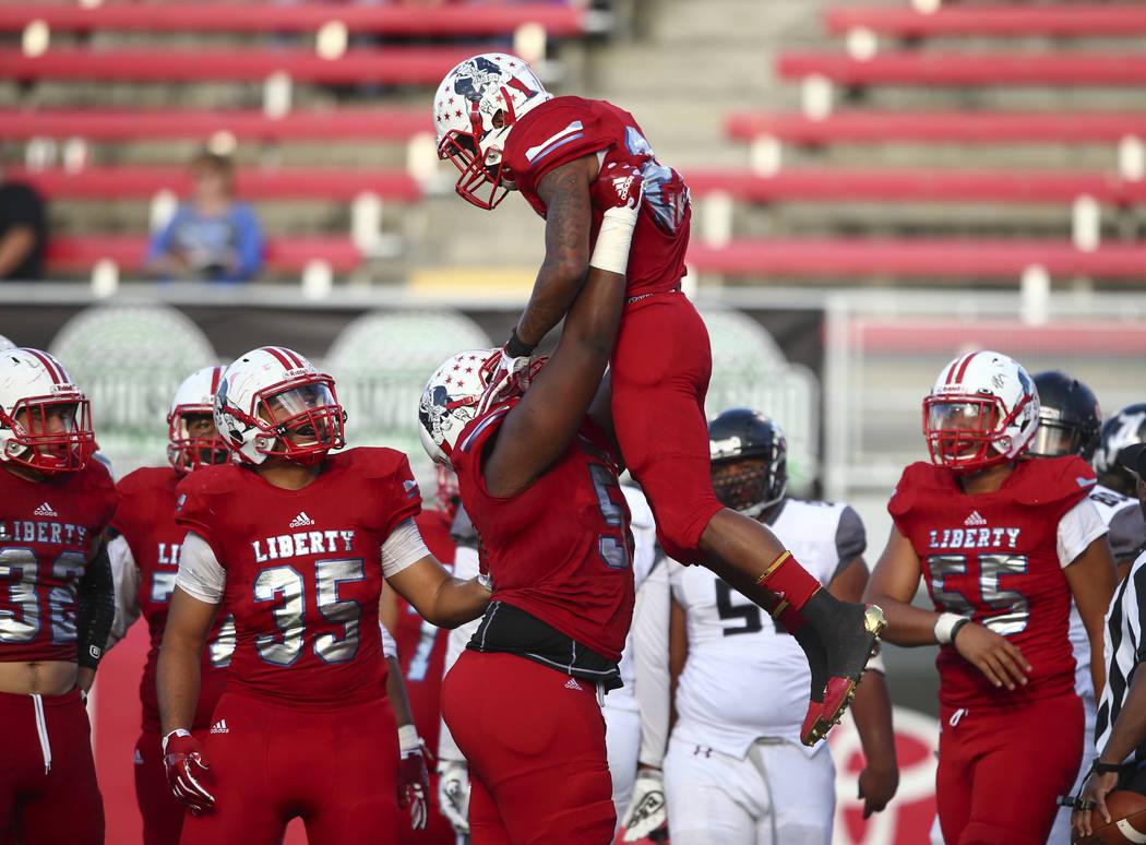 Liberty's Syvone Sistrunk (51) lifts up Liberty's Kishon Pitts (25) after a touchdown from Pitts against Alta during a football game at Sam Boyd Stadium in Las Vegas on Saturday, Sept. 9, 2017. Li ...