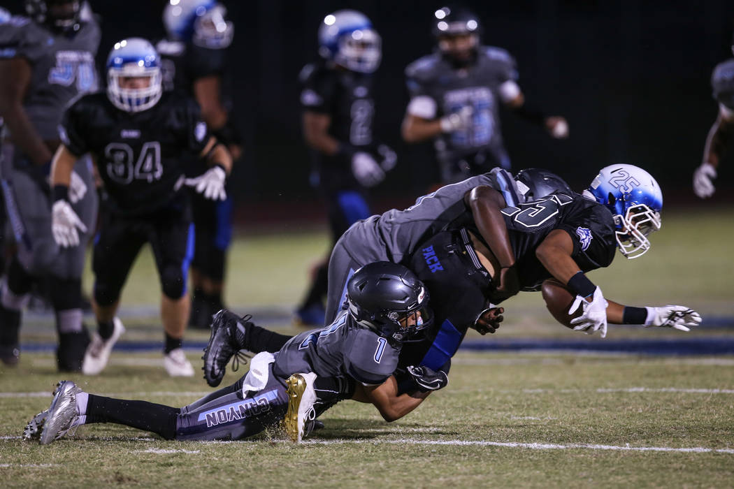 Basic's Jordan Gallegos (25) is tackled by Canyon Springs' TyՓhon Jamal-Brown (1) and Tyjohn Francis (44) during the first quarter of a football game at Basic High School in Henderson, Frida ...