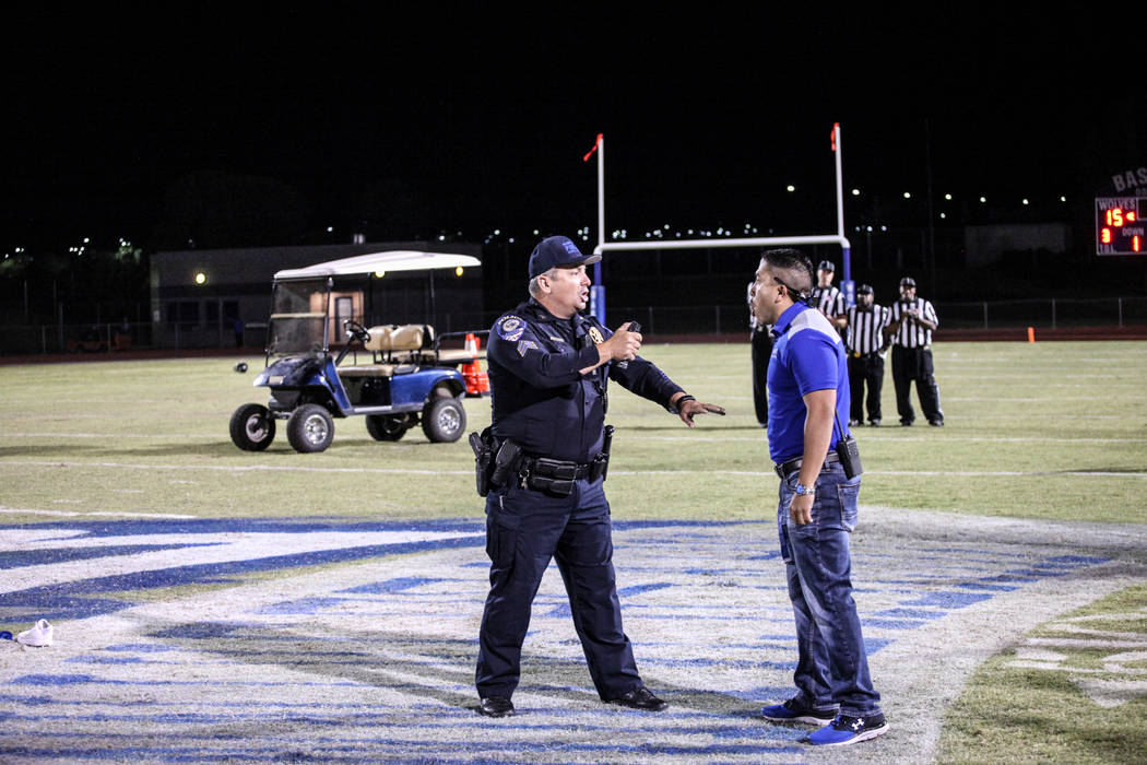 A police officer points pepper spray toward a Basic football staff after dispersing a brawl between Canyon Springs and Basic Academy's football teams at the end of a game at Basic High School in H ...