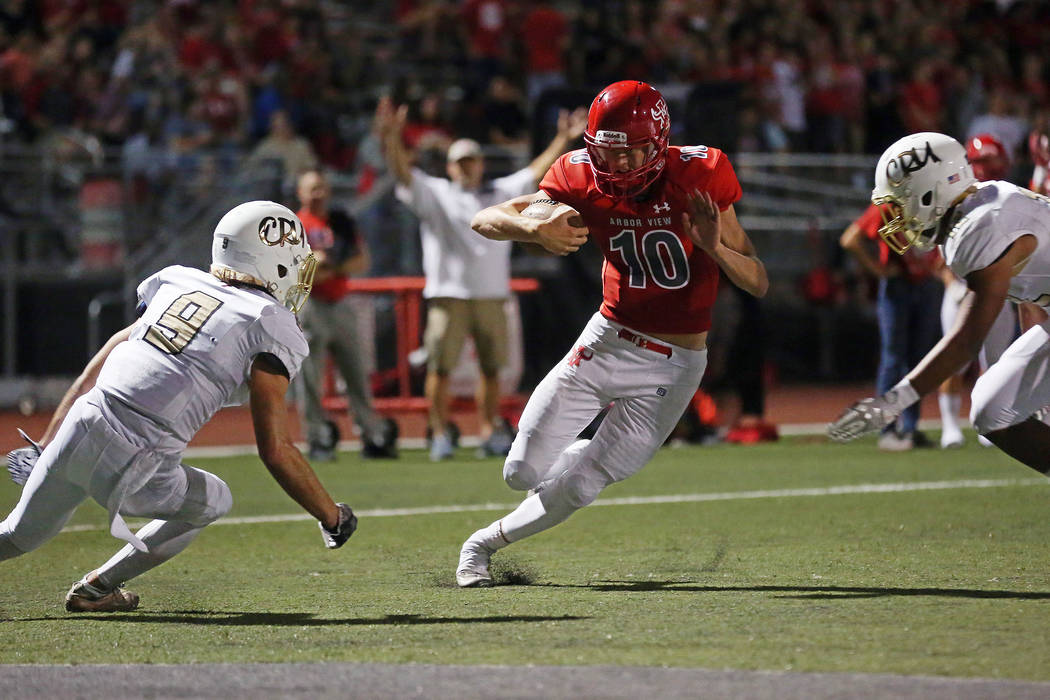 Arbor View quarterback Logan Bollinger, center, attempts to office a tackle from Faith Lutheran players Keagan Touchstone, left, and Ma'a Gaoteote, right, during the first half of the game at Arbo ...