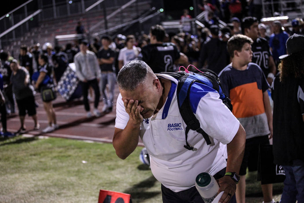 A Basic football staff flushes his eyes after being pepper sprayed by a police officer after a brawl between Canyon Springs and Basic Academy's football teams at the end of a game at Basic High Sc ...