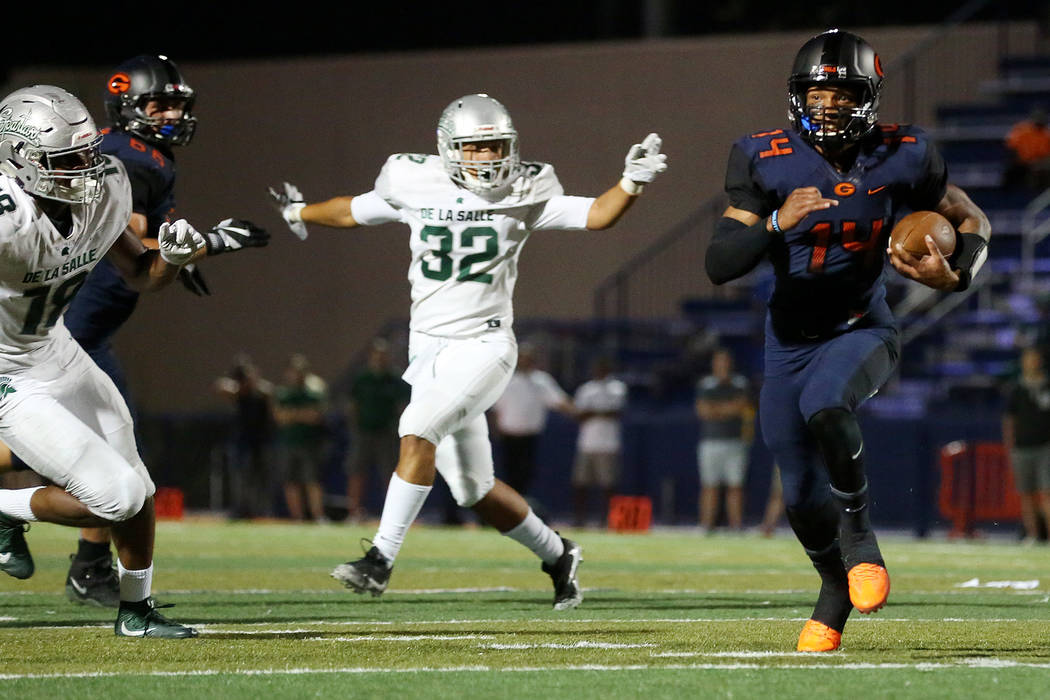 Bishop Gorman's Dorian Thompson-Robinson (14) runs the ball as he avoids tackles from De La Salle players during the first half of the game at Bishop Gorman High School on Saturday, Sept. 16, 2017 ...