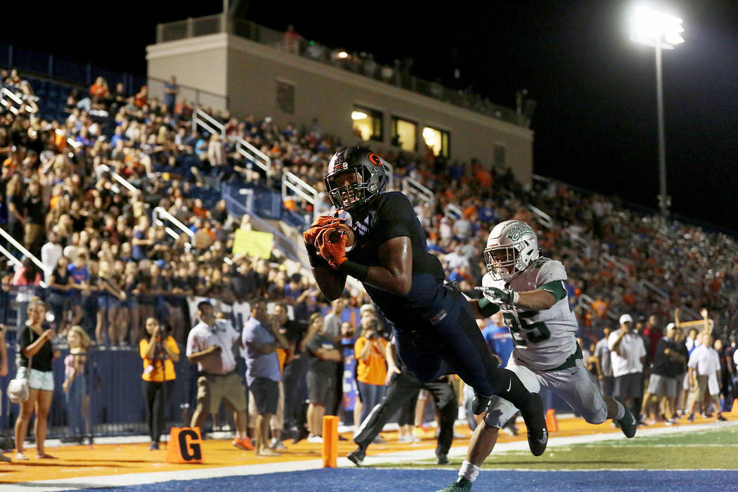 Bishop Gorman's Brevin Jordan dives into the end zone for a touchdown as De La Salle player Kairee Robinson (25) tries to defend during the first half of the game at Bishop Gorman High School on S ...