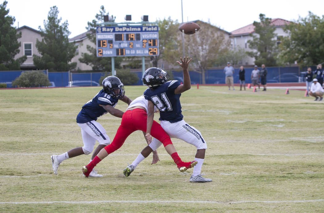 Shadow Ridge's Kaejin Smith-Bejgrowicz (21) intercepts a pass intended for Arbor View's Gregory Welchman, center, during a football game at Shadow Ridge High School on Saturday, Sept. 23, 2017, in ...