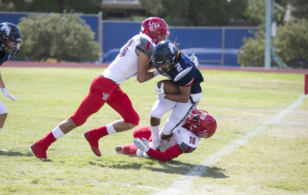 Shadow Ridge's Elisha Young (2) is stopped by Arbor View's Darius Harrison (19) and Deago Stubbs (23) during a football game at Shadow Ridge High School on Saturday, Sept. 23, 2017, in Las Vegas.  ...