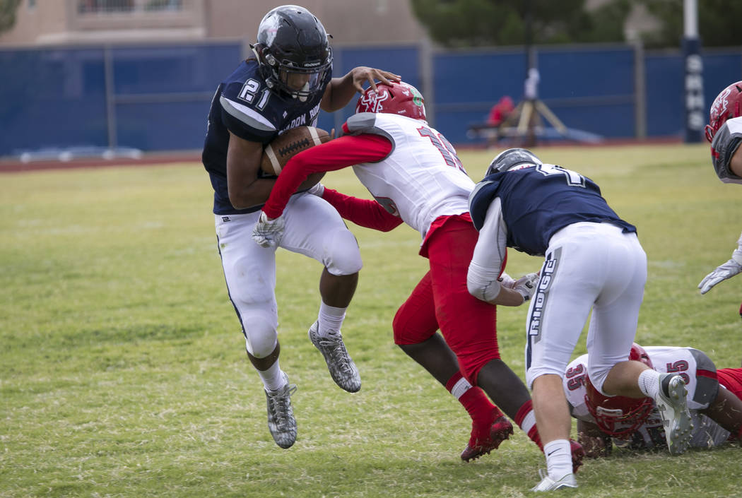 Shadow Ridge's Kaejin Smith-Bejgrowicz (21) is tackled by Arbor View's Darius Harrison (19) during a football game at Shadow Ridge High School on Saturday, Sept. 23, 2017, in Las Vegas. Richard Br ...