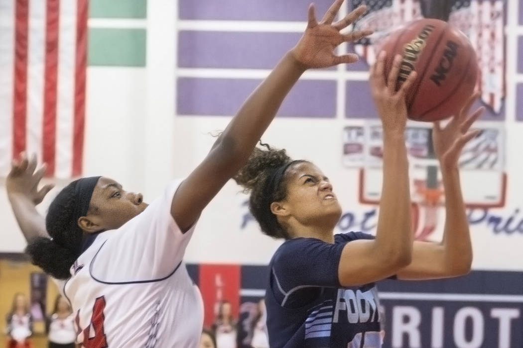 Foothills Rae Burrell (12) drives past Liberty's Dre'una Edwards (44) during the Falcons road matchup with the Patriots  on Monday, Jan. 9, 2017, at Liberty High School, in Las Vegas. Benjamin Hag ...