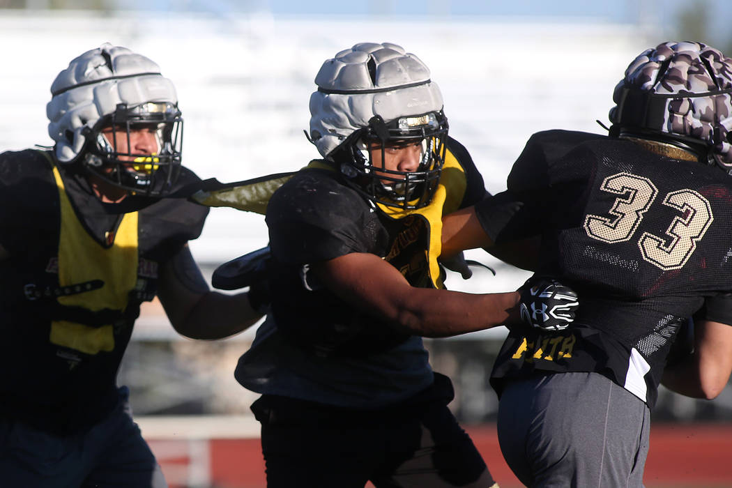 Faith Lutheran football player Ma'a Gaoteote, center, attempts to take down teammate Conor Paravia, right, during a play during practice at Faith Lutheran High School in Las Vegas, Tuesday, Sept.  ...