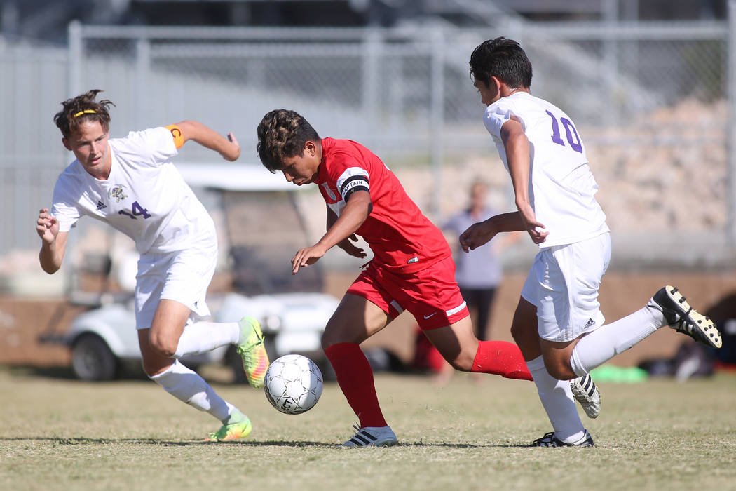 Sunrise Mountain players Julian Herrera (14) and Angel Arreola (10) chase after Western player Juan Arredondo-Alvarez (5) during a game at Sunrise Mountain High School in Las Vegas, Wednesday, Sep ...