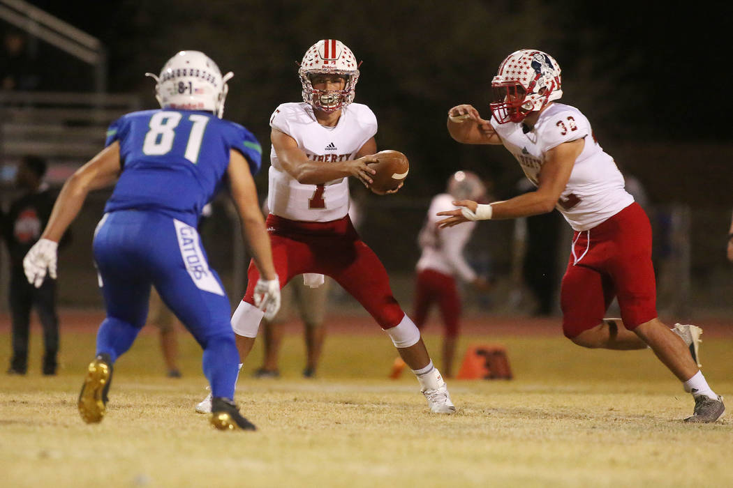 Liberty quarter back Kenyon Oblad (7) hands the ball off to Kyle Beaudry (32) during the first half of a game against Green Valley at Green Valley High School in Henderson, Thursday, Sept. 28, 201 ...