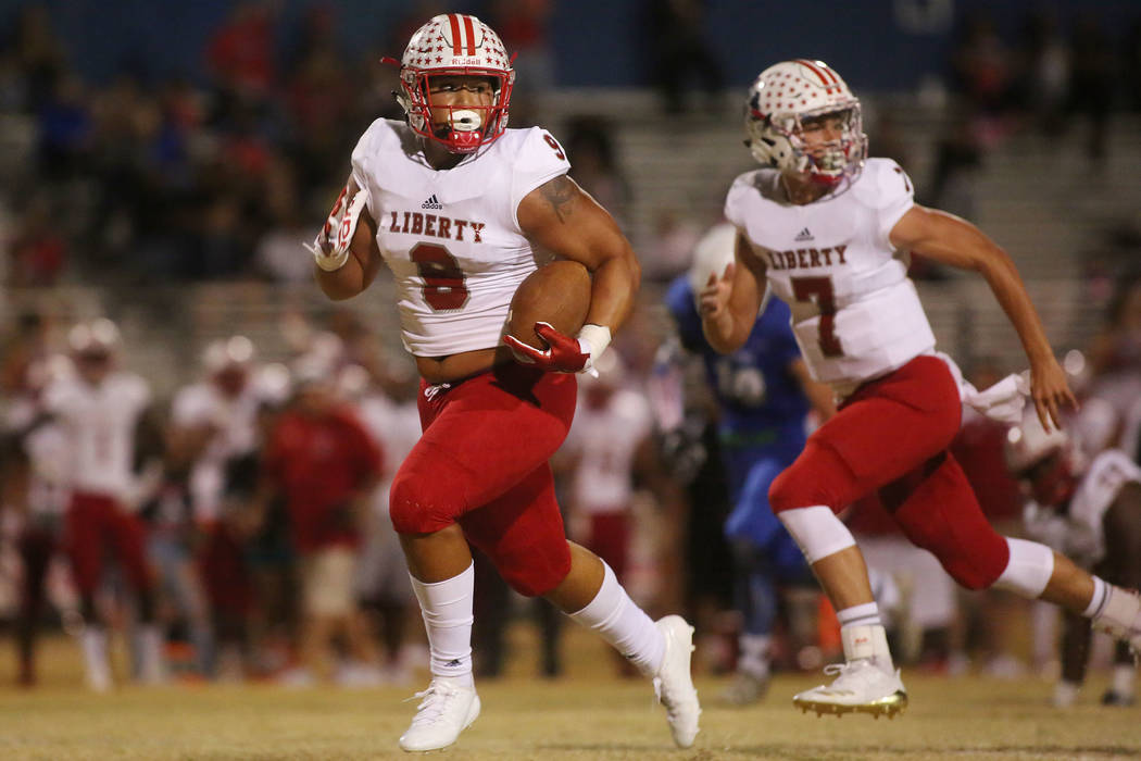 Liberty player Austin Fiaseu (8) runs the ball to the end zone for a touchdown during the first half of a game against Green Valley at Green Valley High School in Henderson, Thursday, Sept. 28, 20 ...