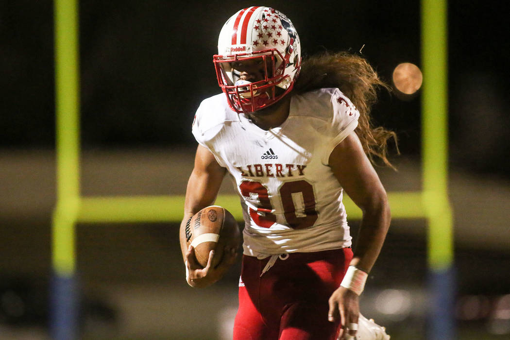 Liberty player Zyrus Fiaseu (30) runs the ball to score a touchdown during the first half of a game against Green Valley at Green Valley High School in Henderson, Thursday, Sept. 28, 2017. Bridget ...