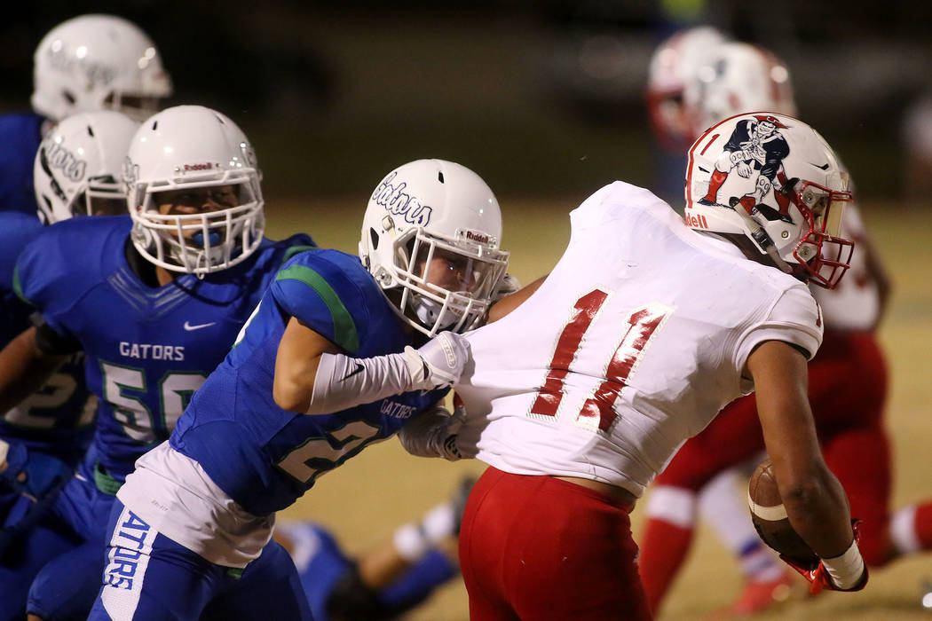 Green Valley player Stetler Harms (23) attempts to takedown Liberty player Jake Dedeaux (11) during the first half a game at Green Valley High School in Henderson, Thursday, Sept. 28, 2017. Bridge ...