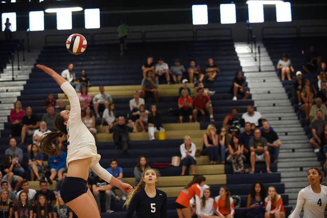 Shadow Ridge's Whittnee Nihipali (15) spikes the ball against Bishop Gorman defenders during their volleyball match played at Shadow Ridge's gym in Las Vegas on Tuesday, Aug. 30 2016. Shadow Ridge ...