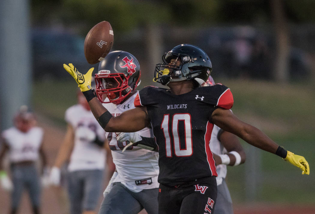Las Vegas High School Wildcats running back Elijah Hicks prepares for the catch as Arbor View High School Aggie linebacker Cameron Phillips runs from behind at Las Vegas High School on Friday, Aug ...