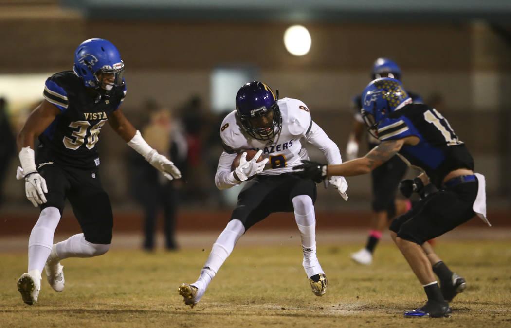 Durango's Johrdan Collins (8) runs the ball as Sierra Vista's Kaika Faatiliga (36) and Jaxson Zibert, right, look to tackle during a football game at Sierra Vista High School in Las Vegas on Frida ...