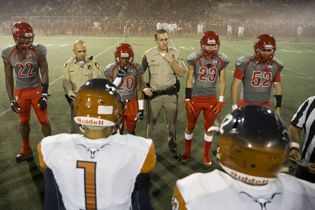 Arbor View players joined by honorary team captains and Las Vegas police officers Marco Crete, left, and Jordan Miller take the field for the coin toss before the football game against Legacy at A ...