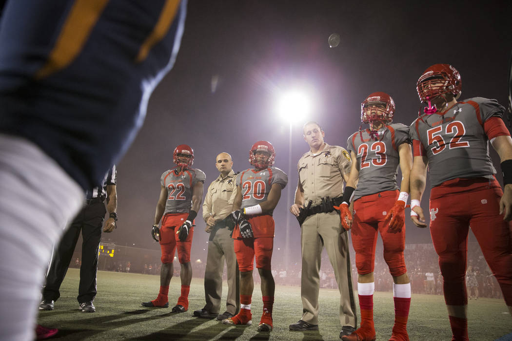 Legacy and Arbor View players joined by honorary team captains and Las Vegas police officers Marco Crete, left, and Jordan Miller watch the coin toss before the football game at Arbor View High Sc ...