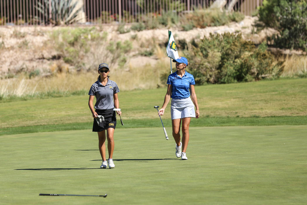 Clark's Riana Mission, left, and Bishop Gorman's Hunter Pate, right, walk during the Class 4A Sunrise and Sunset Region girls golf tournaments at Bearճ Best Golf Club in Las Vegas, Tuesday,  ...