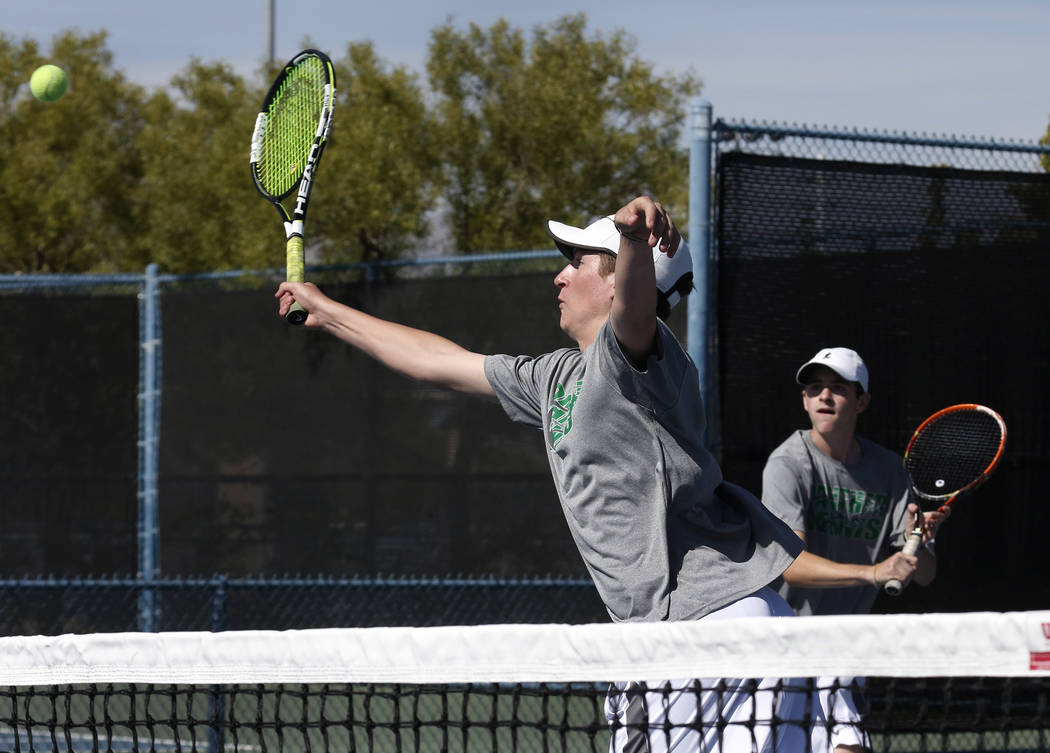 Palo Verde doubles player Travis Clingman returns the ball against Clark High as his tennis partner Jack Hughes looks on during the Class 4A state finals at Darling Tennis Center Friday, Oct. 20,  ...