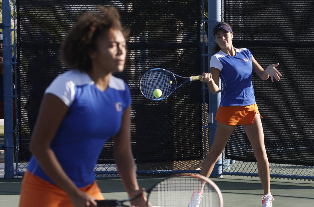 Bishop Gorman's Olivia Balelo returns the ball against Coronado High's Jessica Duff and Mana Iritani as her tennis partner Giovanna Chaparro, left, looks on during the Class 4A state doubles final ...