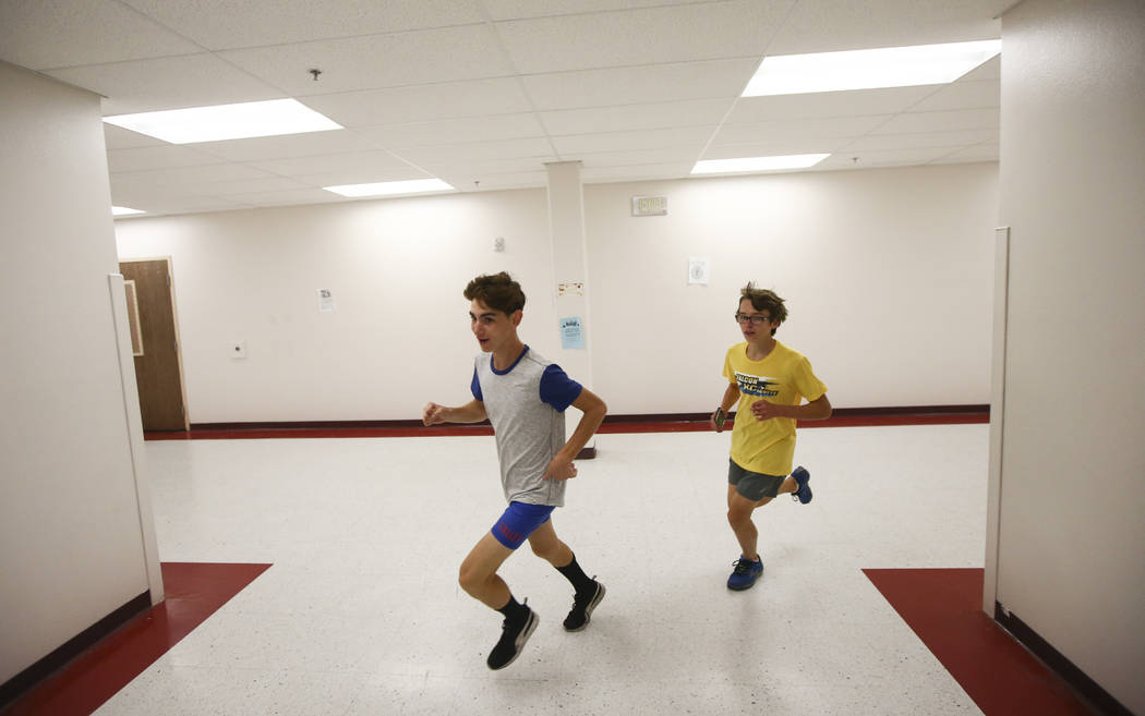 Valley's Donovan Jones, left, warms up in the hallways as cross country practice begins at the high school in Las Vegas on Wednesday, Oct. 25, 2017. Chase Stevens Las Vegas Review-Journal @cssteve ...
