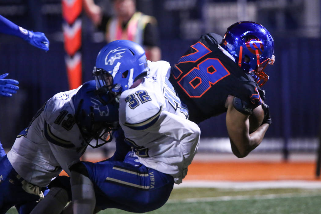 Bishop Gorman's Amod Cianelli (28), right, is tackled by Sierra Vista's Jaxson Zibert (13), left, and Devin Gomez (32), center, during the first quarter of a football game at Bishop Gorman High Sc ...