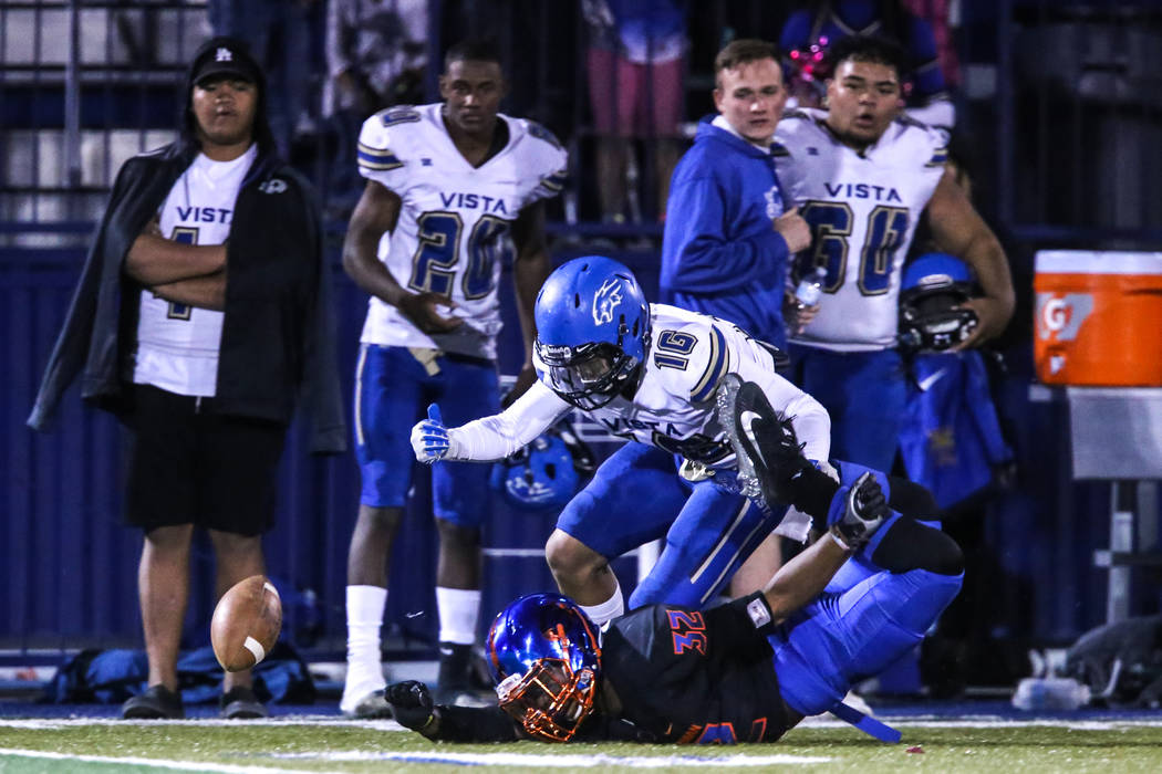 Bishop Gorman's Jojuan Claiborne (32), bottom, falls as Sierra Vista's Tristen Jimenez (16), top, guards him during a pass route in the third quarter of a football game at Bishop Gorman High Schoo ...