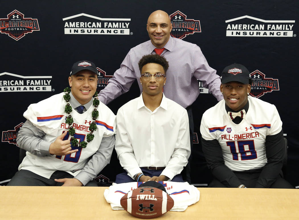 Bishop Gorman's head coach Kenny Sanchez, standing, with offensive guard Jacob Isaia, left, quarterback Dorian Thompson-Robinson and tight end Brevin Jordan, right, after his players received thei ...