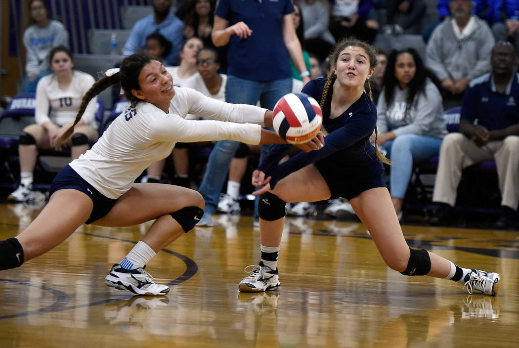 Shadow Ridge's Kizzy Rodriguez, left, and Braedyn Peters dig for the ball against Bishop Gorman during a class 4A Sunset Region final volleyball game at Durango High School Friday, Nov. 3, 2017, i ...