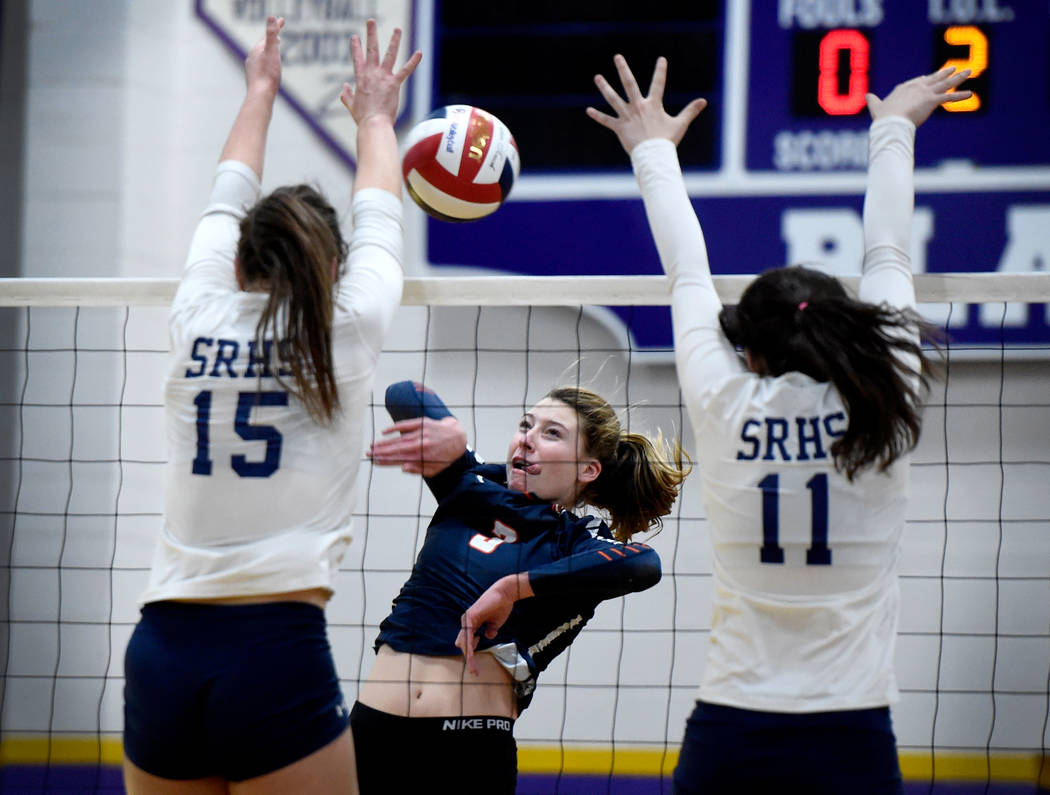 Bishop Gorman's Tommi Stockham, center, hits the ball against Shadow Ridge's Whittnee Nihipali (15) and Natalie Nihipali during a class 4A Sunset Region final volleyball game at Durango High Schoo ...