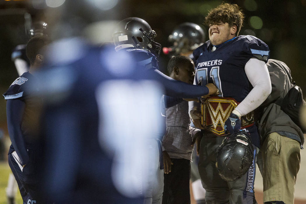 Canyon Spring's Donovan Wolfe (71) attempts to fit a wrestling belt around his wait during their football playoff game against Basic at Canyon Spring High School in Las Vegas, Friday, Nov. 3, 2017 ...