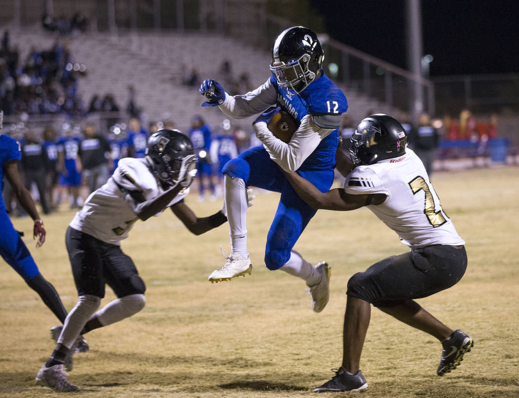 Desert Pines running back Jyden King (12) jumps into the end zone for a touchdown during the Class 3A state quarterfinal football game against Sunrise Mountain High School at Desert Pines High Sch ...