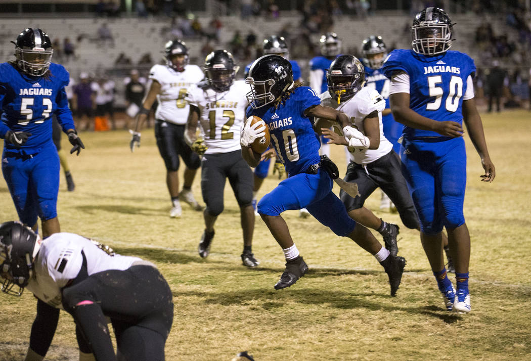 Desert Pines running back Devin McGee (10) breaks through Sunrise Mountain defenders for a touchdown during the Class 3A state quarterfinal football game at Desert Pine High School in Las Vegas, T ...