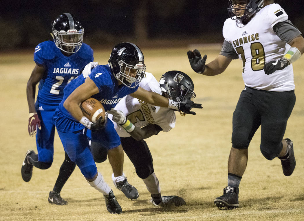 Desert Pines wide receiver Branden Thomas (4) stiff-arms Sunrise Mountain defender Xavier Kyle (5) during the Class 3A state quarterfinal football game at Desert Pine High School in Las Vegas, Thu ...