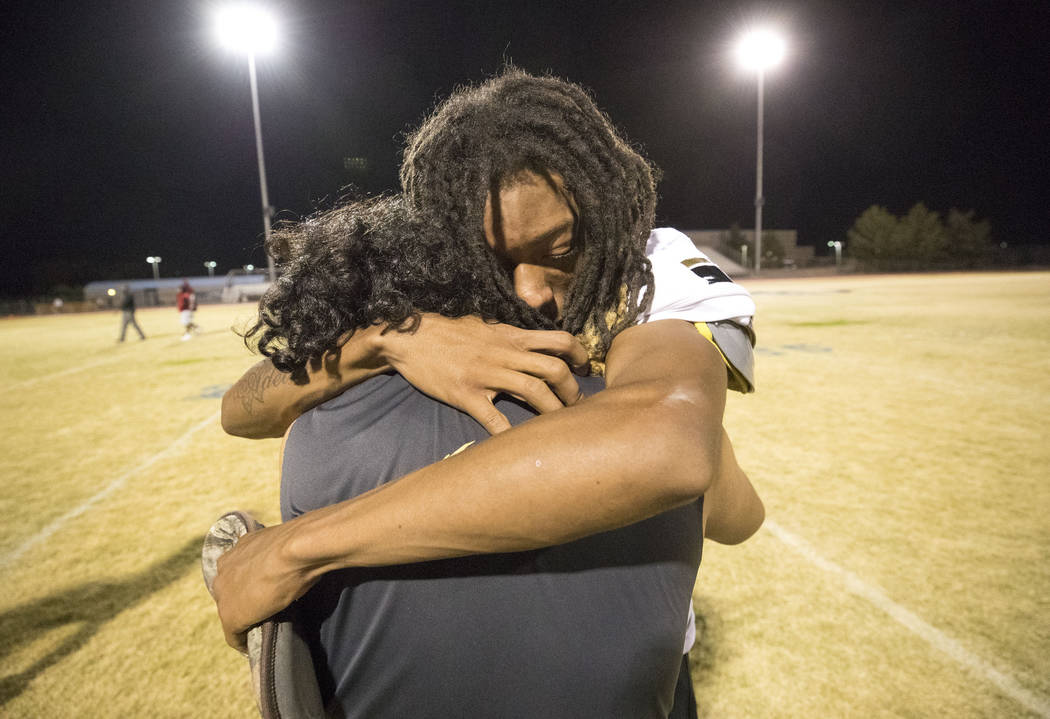 Sunrise Mountain linebacker Gabriel Razo, foreground, consoles running back Trayvon Ward after losing to Desert Pines in the Class 3A state quarterfinal football game at Desert Pine High School in ...