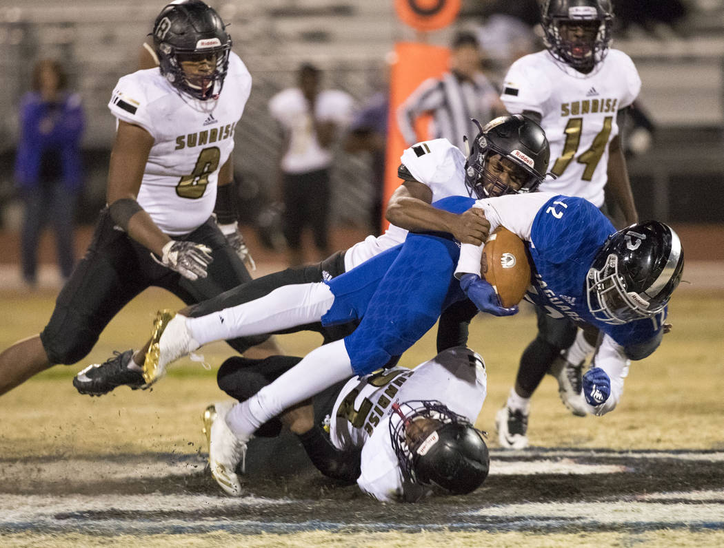 Desert Pines running back Jyden King (12) is brought down by Sunrise Mountain defenders during the Class 3A state quarterfinal football game at Desert Pine High School in Las Vegas, Thursday, Nov. ...