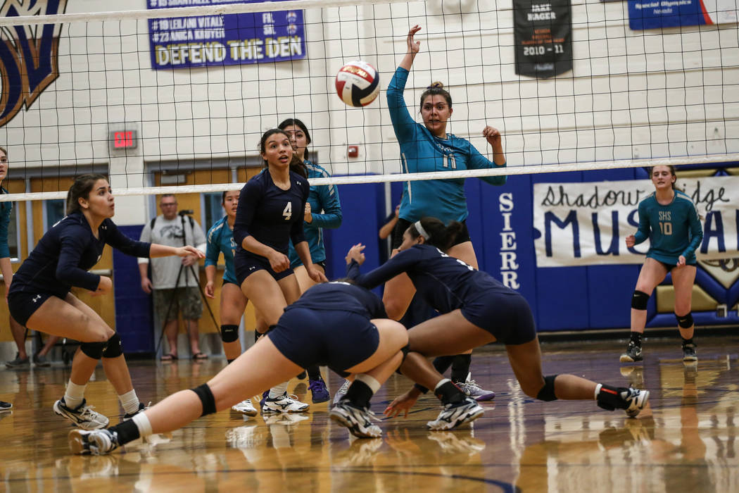 Shadow Ridge scrambles to hit the ball after Silverado's Sydney Berenyi (11), right, hit it across the net during game two of a volleyball game at Sierra Vista High School in Las Vegas, Monday, No ...