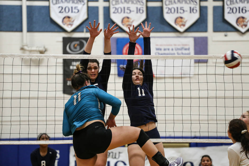 Shadow Ridge's Whittnee Nihipali (15), center, and Kahea Nihipali (11), right, jump as they block a shot from Silverado's Sydney Berenyi (11), left, during game three of a volleyball game at Sierr ...