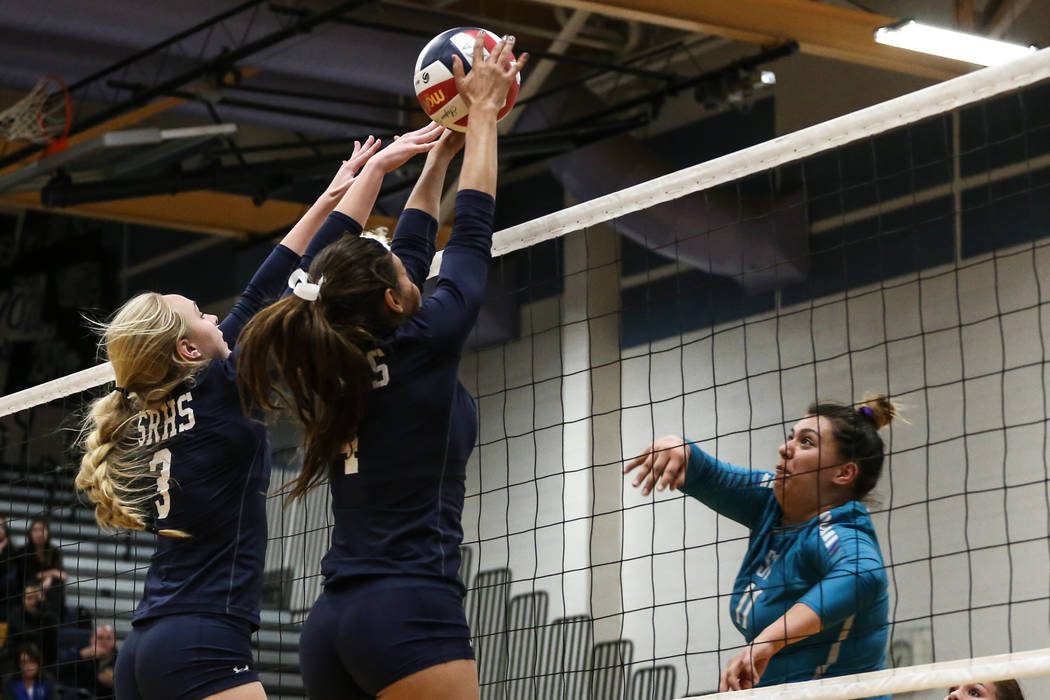 Shadow Ridge's Madison Norr (3), left, and Kizzy Rodriguez (4), center, block a shot by Silverado's Sydney Berenyi (11), right, during game two of a volleyball game at Sierra Vista High School in  ...